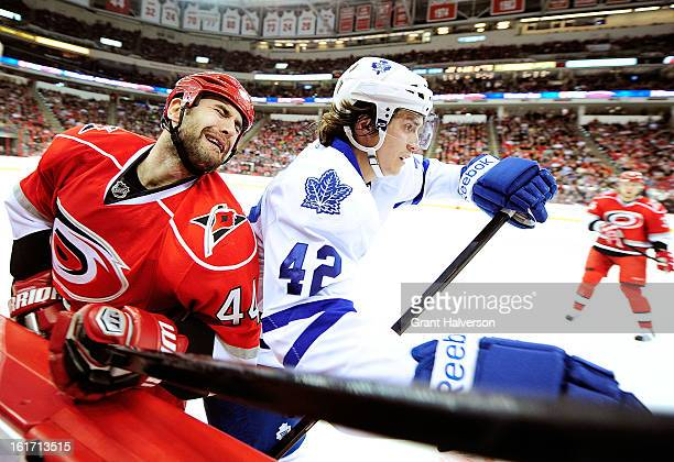 Tyler Bozak of the Toronto Maple checks Jay Harrison of the Carolina Hurricanes during play at PNC Arena on February 14, 2013 in Raleigh, North...