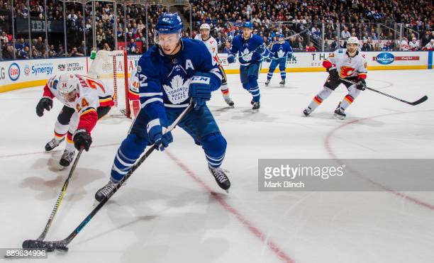 Tyler Bozak of the Toronto Maple Leafs battles with Travis Hamonic of the Calgary Flames during the first period at the Air Canada Centre on December...