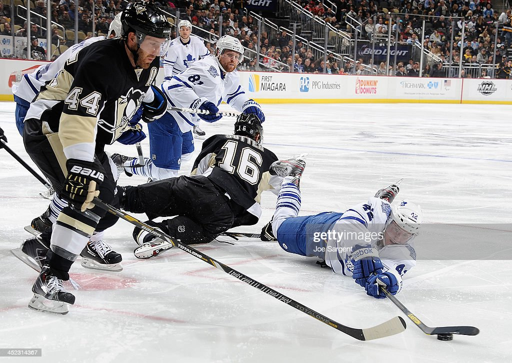 Tyler Bozak #42 of the Toronto Maple Leafs dives for the loose puck in front of Brooks Orpik #44 of the Pittsburgh Penguins on November 27, 2013 at Consol Energy Center in Pittsburgh, Pennsylvania.