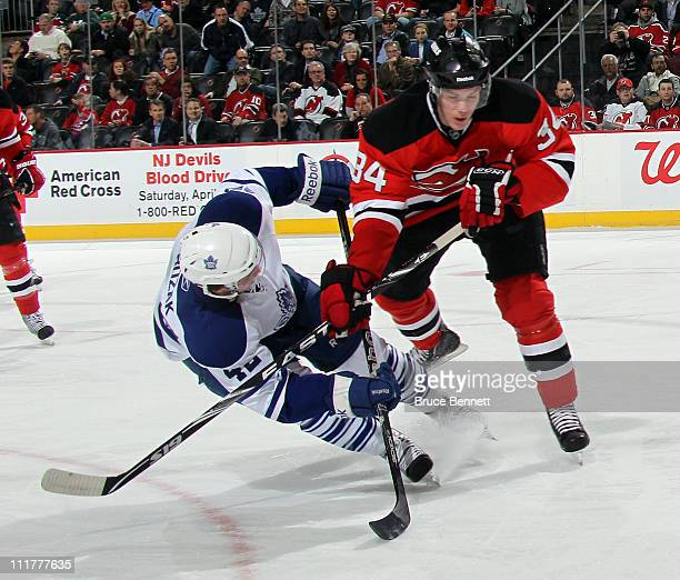 Tyler Bozak of the Toronto Maple Leafs is dumped by Mark Fayne of the New Jersey Devils at the Prudential Center on April 6, 2011 in Newark, New...