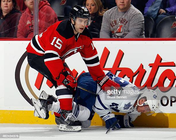 Tyler Bozak of the Toronto Maple Leafs is tripped up by Tuomo Ruutu of the New Jersey Devils during the first period at the Prudential Center on...