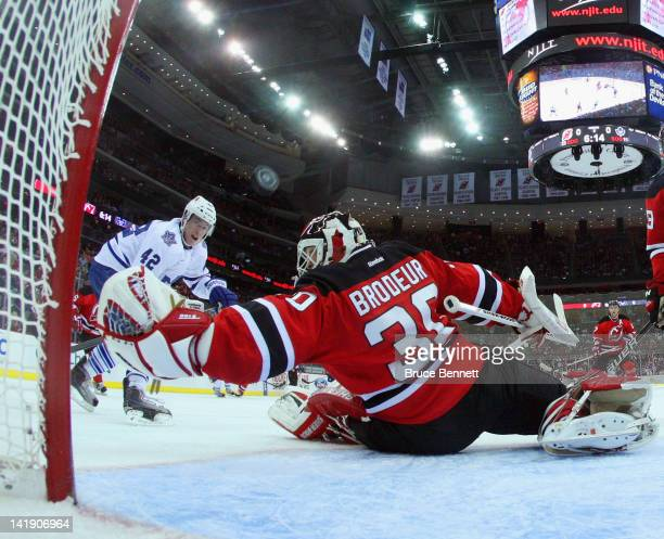 Tyler Bozak of the Toronto Maple Leafs watches a shot sail past Martin Brodeur of the New Jersey Devils at the Prudential Center on March 23, 2012 in...