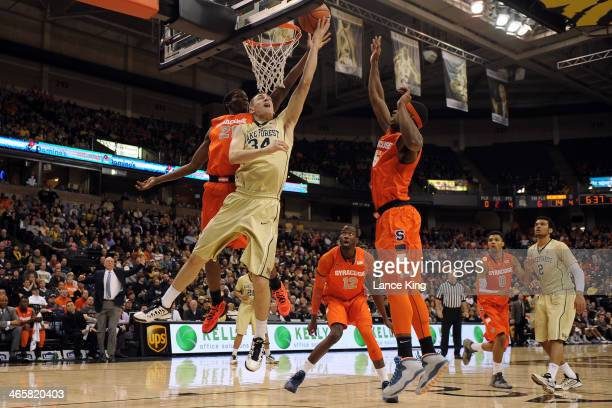 Tyler Cavanaugh of the Wake Forest Demon Deacons goes to the hoop against Tyler Roberson of the Syracuse Orange at Lawrence Joel Coliseum on January...