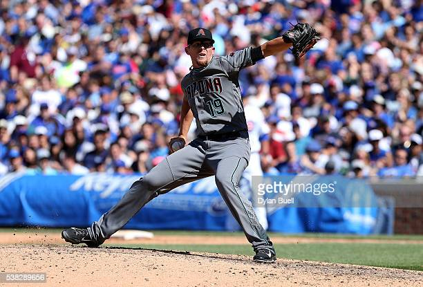 Tyler Clippard of the Arizona Diamondbacks trips while going through his windup in the eighth inning against the Chicago Cubs at Wrigley Field on...