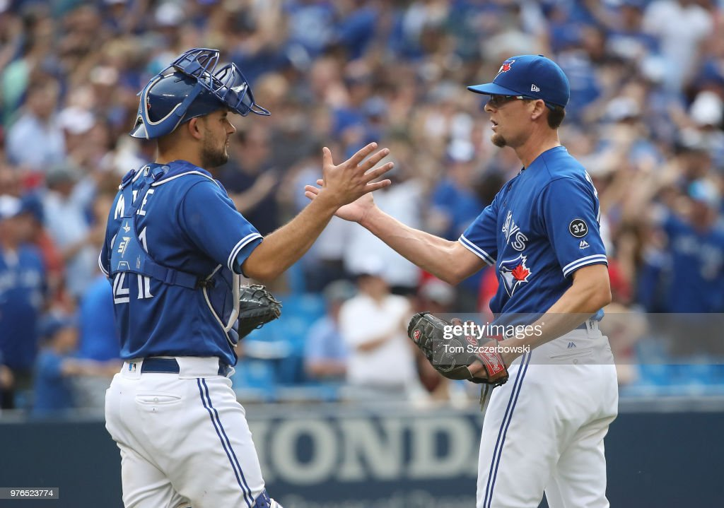 Tyler Clippard #36 of the Toronto Blue Jays celebrates their victory with Luke Maile #21 during MLB game action against the Washington Nationals at Rogers Centre on June 16, 2018 in Toronto, Canada.