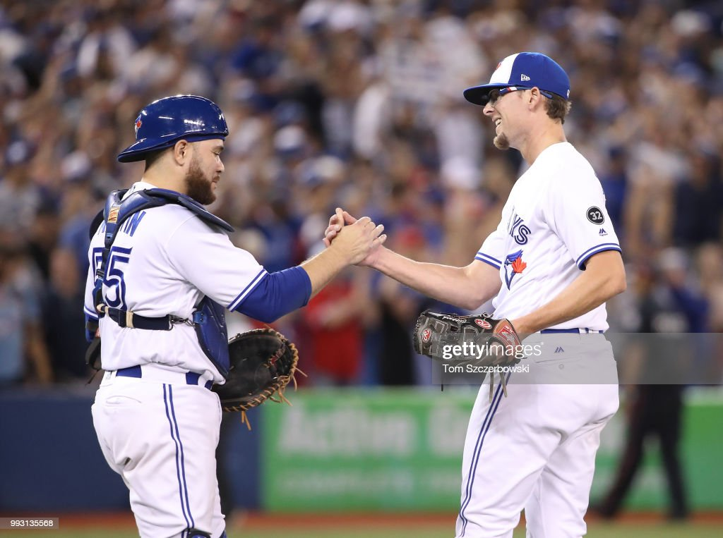 Tyler Clippard #36 of the Toronto Blue Jays celebrates their victory with Russell Martin #55 during MLB game action against the New York Yankees at Rogers Centre on July 6, 2018 in Toronto, Canada.