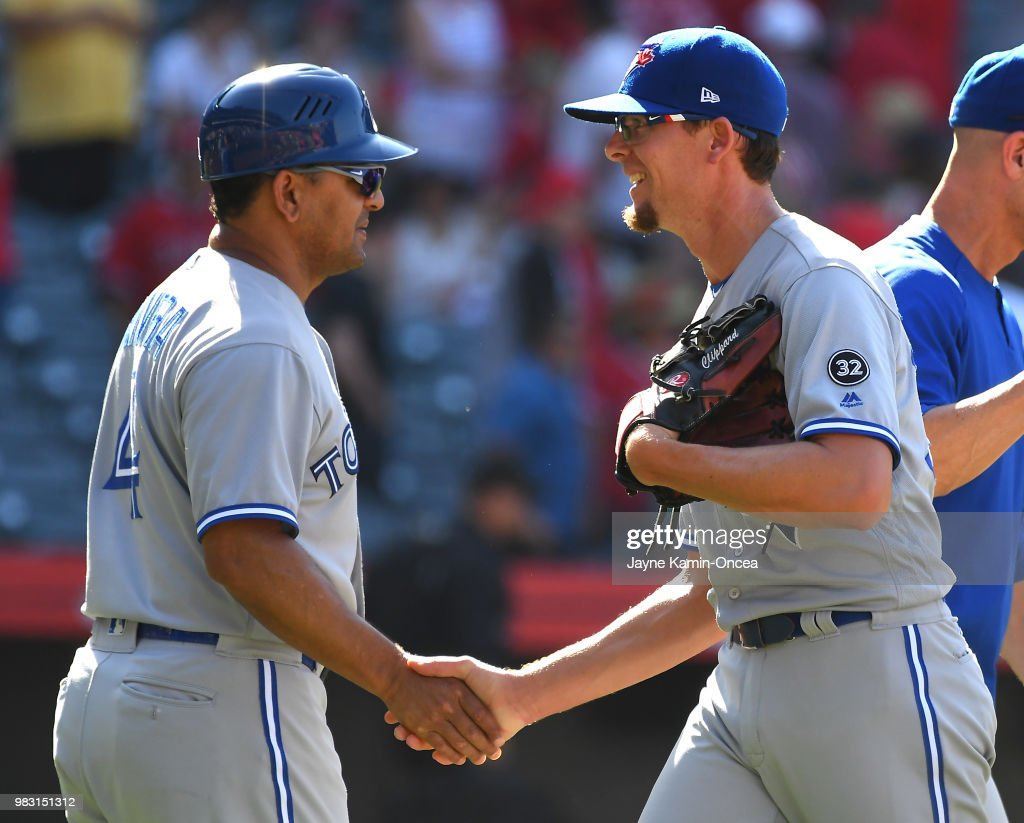 Tyler Clippard #36 shakes hands with third base coach Luis Rivera #4 of the Toronto Blue Jays after earning a save in the tenth inning of the game against the Los Angeles Angels of Anaheim at Angel Stadium on June 24, 2018 in Anaheim, California.