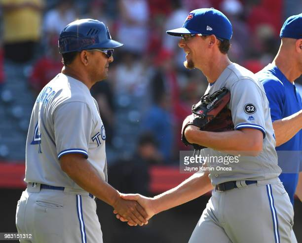 Tyler Clippard shakes hands with third base coach Luis Rivera of the Toronto Blue Jays after earning a save in the tenth inning of the game against...