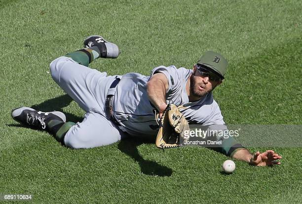 Tyler Collins of the Detroit Tigers dives unsucessfully to try and catch a ball hit by Jose Abreu of the Chicago White Sox in the 8th inning at...