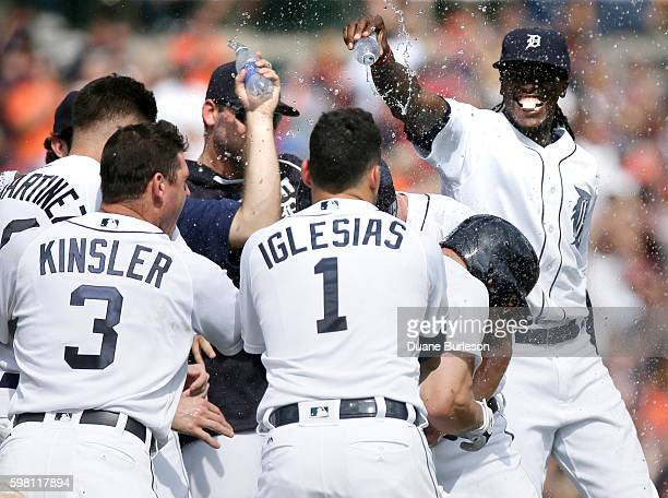 Tyler Collins of the Detroit Tigers has water poured on him by Cameron Maybin of the Detroit Tigers right while celebrating with Ian Kinsler of the...
