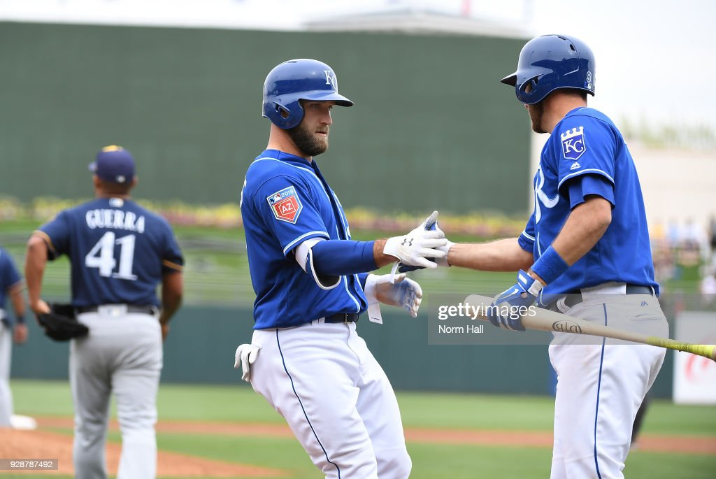 Tyler Collins #7 of the Kansas City Royals is congratulated by teammate Drew Butera #9 after scoring on a sacrifice fly by Ryan Goins #1 during the second inning of a spring training game against the Milwaukee Brewers at Surprise Stadium on March 7, 2018 in Surprise, Arizona.