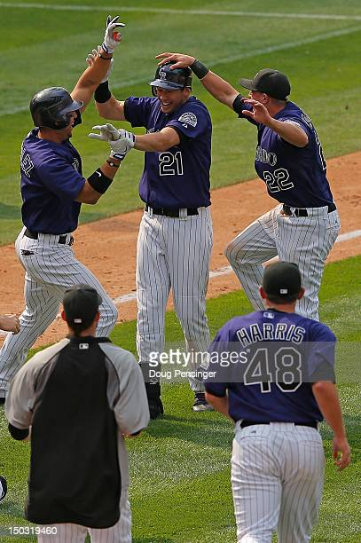 Tyler Colvin of the Colorado Rockies celebrates his game winning walk off two RBI double with Carlos Gonzalez and Jordan Pacheco of the Colorado...