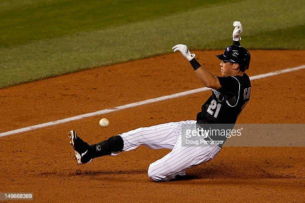 Tyler Colvin of the Colorado Rockies races the baseball as he slides safely into thirdbase with an RBI triple in the sixth inngin at Coors Field on...