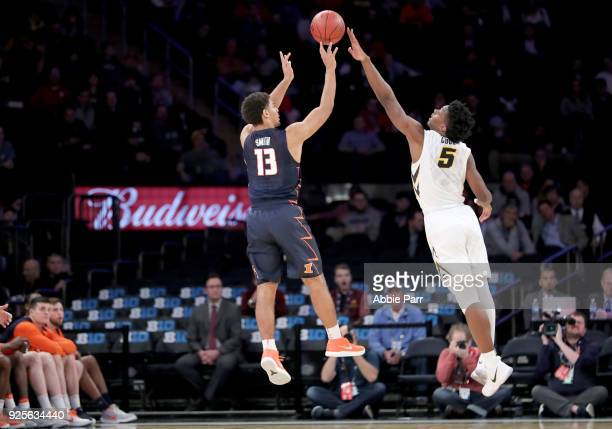 Tyler Cook of the Iowa Hawkeyes blocks a shot by Mark Smith of the Illinois Fighting Illini in the second half during the Big Ten Basketball...