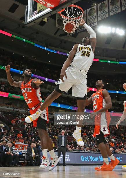 Tyler Cook of the Iowa Hawkeyes dunks over Kipper Nichols of the Illinois Fighting Illini at the United Center on March 14 2019 in Chicago Illinois...