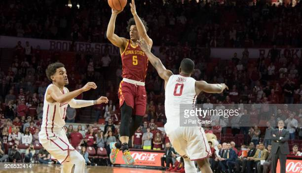 Tyler Cook of the Iowa Hawkeyes goes up between Trae Young of the Oklahoma Sooners and Christian James 0 of the Oklahoma Sooners passing to the ball...
