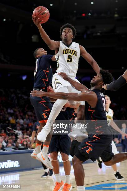Tyler Cook of the Iowa Hawkeyes takes a shot against Kipper Nichols of the Illinois Fighting Illini in the second half during the Big Ten Basketball...