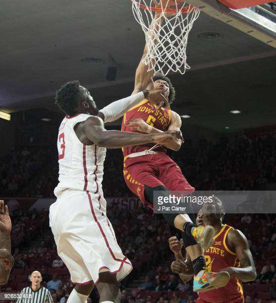 Tyler Cook#5 of the Iowa Hawkeyes dunks the ball over Khadeem Lattin of the Oklahoma Sooners during the first half of a NCAA college basketball game...