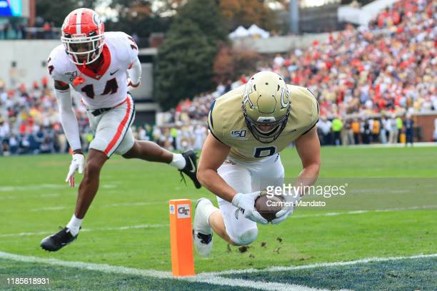 Tyler Davis of the Georgia Tech Yellow Jackets scores a touchdown in front of DJ Daniel of the Georgia Bulldogs during the first half of the game at...
