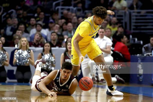 Tyler Davis of the Texas AM Aggies and Isaiah Livers of the Michigan Wolverines go for a loose ball in the second half in the 2018 NCAA Men's...