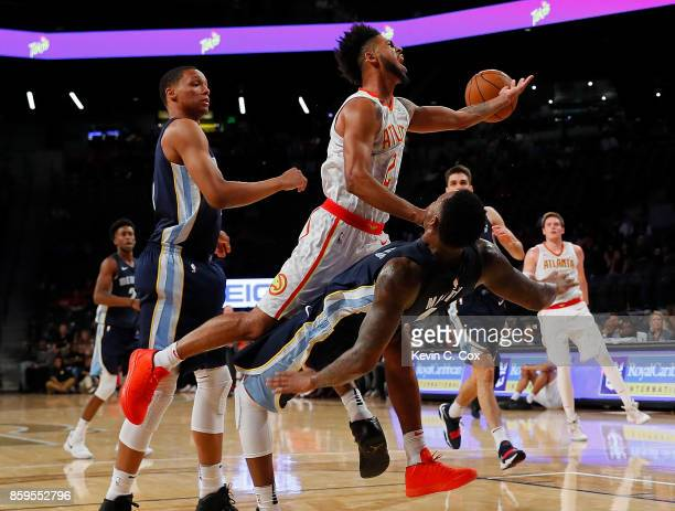 Tyler Dorsey of the Atlanta Hawks drives between Ivan Rabb and Jarell Martin of the Memphis Grizzlies at McCamish Pavilion on October 9 2017 in...