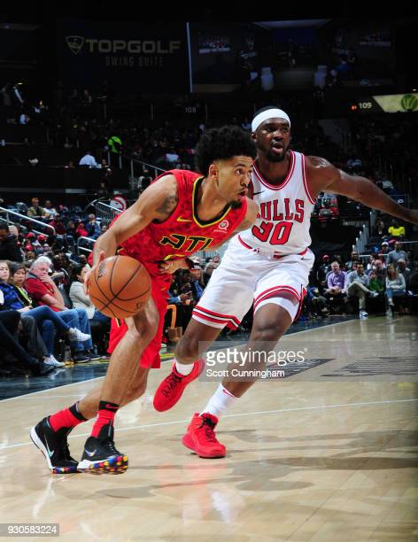 Tyler Dorsey of the Atlanta Hawks handles the ball against Noah Vonleh of the Chicago Bulls on March 11 2018 at Philips Arena in Atlanta Georgia NOTE...