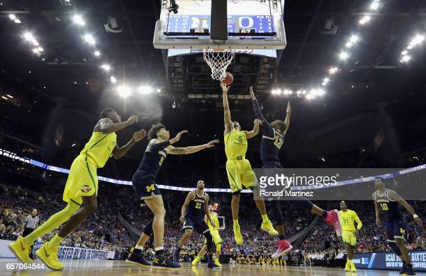 Tyler Dorsey of the Oregon Ducks battles for the ball with DJ Wilson and MuhammadAli AbdurRahkman of the Michigan Wolverines in the second half...