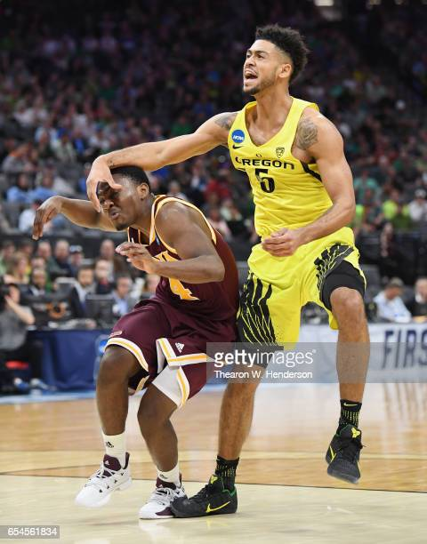 Tyler Dorsey of the Oregon Ducks makes contact with Schadrac Casimir of the Iona Gaels in the first half during the first round of the 2017 NCAA...