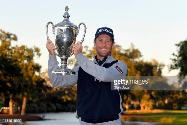 Tyler Duncan celebrates with the winner's trophy after a two hole playoff with Webb Simpson during the final round of The RSM Classic at Sea Island...