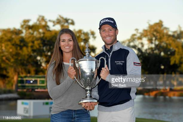 Tyler Duncan celebrates with the winner's trophy and wife Maria after the final round of The RSM Classic at Sea Island Resort Seaside Course on...