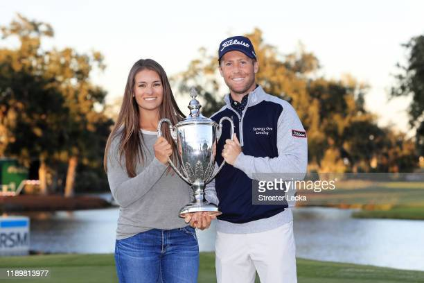 Tyler Duncan of the United States celebrates with the winner's trophy and wife Maria after the final round of the RSM Classic on the Seaside course...