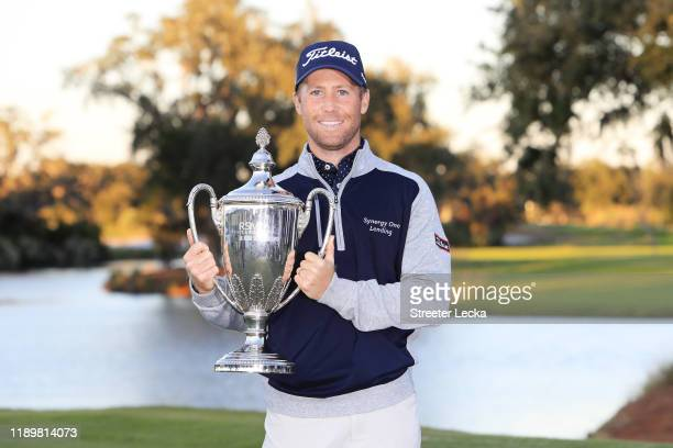 Tyler Duncan of the United States celebrates with the winner's trophy after the final round of the RSM Classic on the Seaside course at Sea Island...