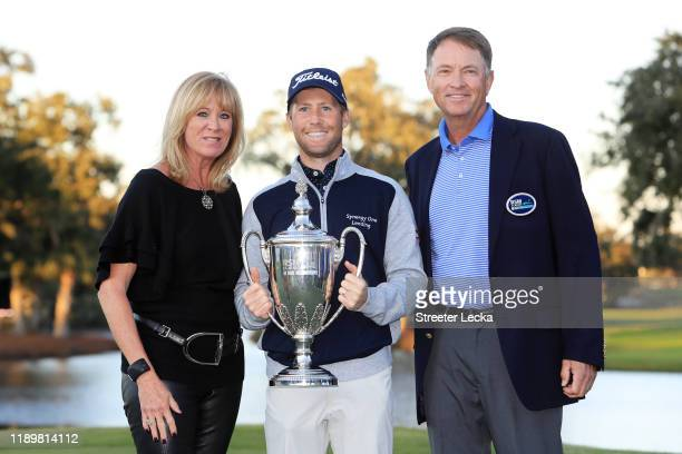 Tyler Duncan of the United States celebrates with the winner's trophy Davis Love III of the United States and Robin Love after the final round of the...