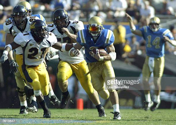 Tyler Ebell of the UCLA Bruins carries the ball while being pursued by Donnie McCleskey of the Cal Golden Bears in the fourth quarter on October 18,...