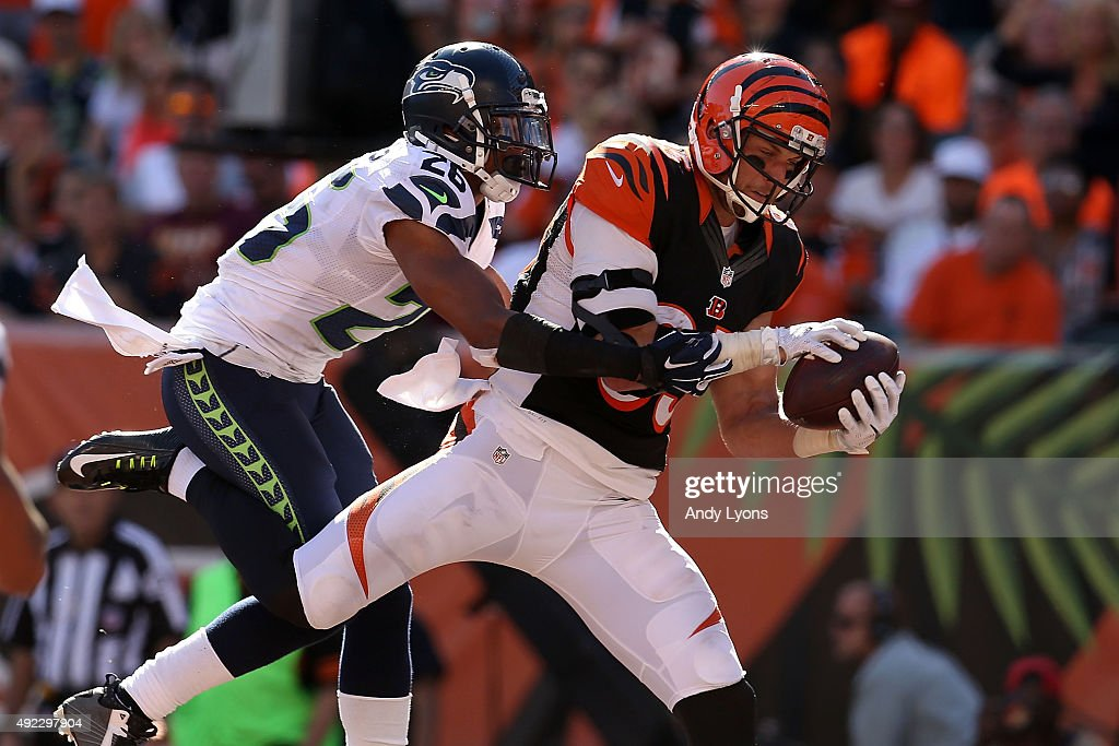 Tyler Eifert #85 of the Cincinnati Bengals catches a pass for his second touchdown of the game while being defended by Cary Williams #26 of the Seattle Seahawks during the fourth quarter at Paul Brown Stadium on October 11, 2015 in Cincinnati, Ohio. Cincinnati defeated Seattle 27-24 in overtime.