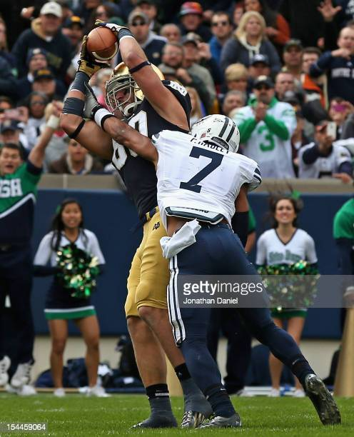 Tyler Eifert of the Notre Dame Fighting Irish catches a touchdown pass under pressure from Preston Hadley of the BYU Courgars at Notre Dame Stadium...
