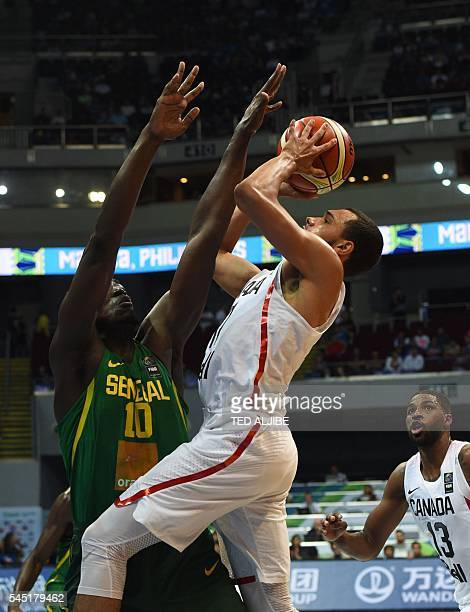 Tyler Ennis of Canada goes up for a shot as Cheikh Mbodj of Senegal defends during their 2016 FIBA Olympic men's qualifying basketball tournament in...
