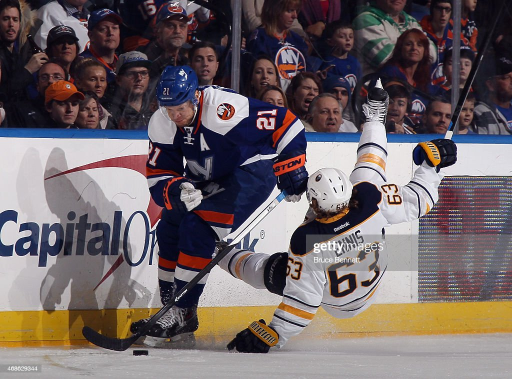 Tyler Ennis #63 of the Buffalo Sabres bounces off Kyle Okposo #21 of the New York Islanders during the first period at the Nassau Veterans Memorial Coliseum on April 4, 2015 in Uniondale, New York.