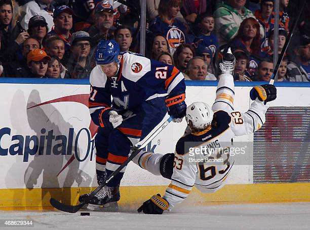 Tyler Ennis of the Buffalo Sabres bounces off Kyle Okposo of the New York Islanders during the first period at the Nassau Veterans Memorial Coliseum...