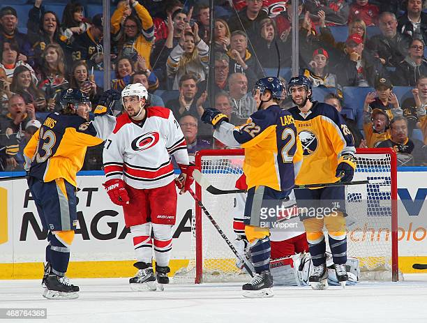Tyler Ennis of the Buffalo Sabres celebrates his second period goal against the Carolina Hurricanes with teammates Johan Larsson and Matt Moulson as...