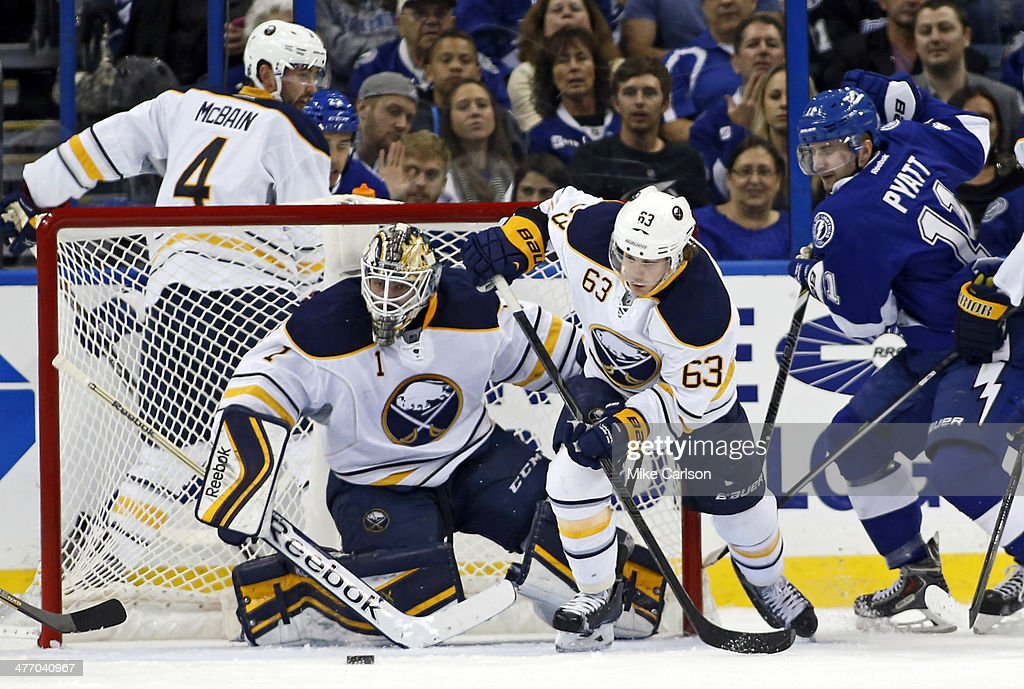 Tyler Ennis #63 of the Buffalo Sabres clears the puck after a save by goalie Jhonas Enroth #1 in front of Tom Pyatt #11 of the Tampa Bay Lightning at the Tampa Bay Times Forum on March 6, 2014 in Tampa, Florida.