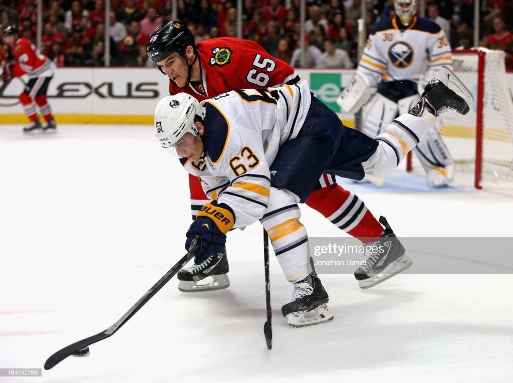 Tyler Ennis #63 of the Buffalo Sabres controls the puck under pressure from Andrew Shaw #65 of the Chicago Blackhawks at the United Center on October 12, 2013 in Chicago, Illinois.