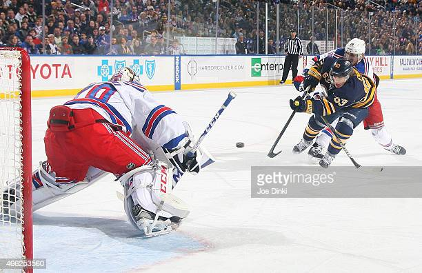 Tyler Ennis of the Buffalo Sabres fires a first period shot against Mackenzie Skapski of the New York Rangers while Marc Staal closes in on March 14...