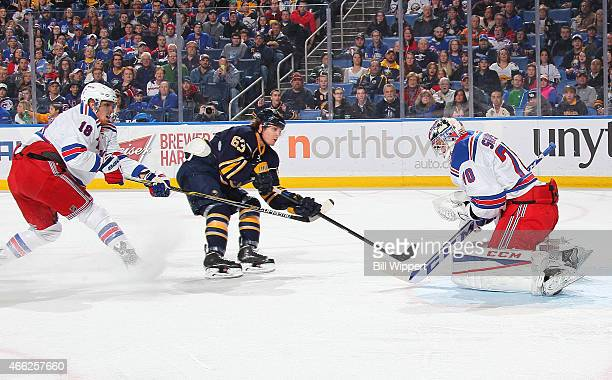 Tyler Ennis of the Buffalo Sabres fires a first period shot that is saved by Mackenzie Skapski of the New York Rangers while Marc Staal closes in on...