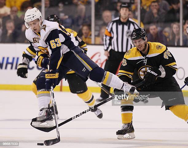 Tyler Ennis of the Buffalo Sabres jumps over the stick of David Krejci of the Boston Bruins and still hangs on to the puck in Game Six of the Eastern...