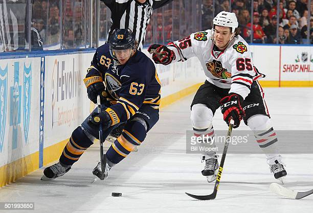 Tyler Ennis of the Buffalo Sabres looks to control the puck while being defended by Andrew Shaw of the Chicago Blackhawks during an NHL game on...