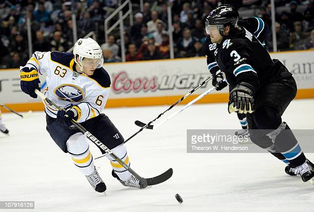 Tyler Ennis of the Buffalo Sabres looks to get control of the puck in front of Douglas Murray of the San Jose Sharks in the third period of an NHL...