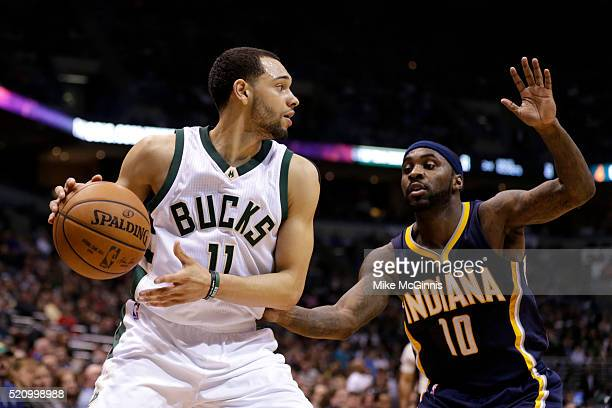 Tyler Ennis of the Milwaukee Bucks dribbles the basketball with Ty Lawson defending during the second quarter at BMO Harris Bradley Center on April...
