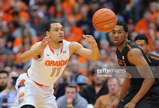 Tyler Ennis of the Syracuse Orange and Garrius Adams of the Miami Hurricanes react to a loose ball during the first half at the Carrier Dome on...