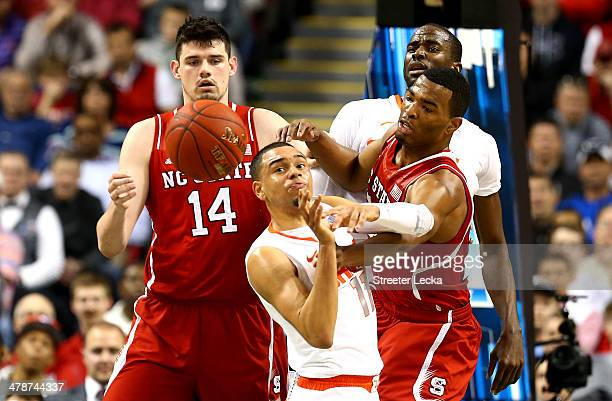 Tyler Ennis of the Syracuse Orange battles for a loose ball against Jordan Vandenberg and TJ Warren of the North Carolina State Wolfpack during the...